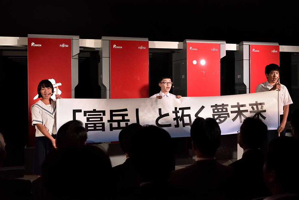 写真:横断幕「「富岳」と拓く夢未来」を掲げる高校生たち