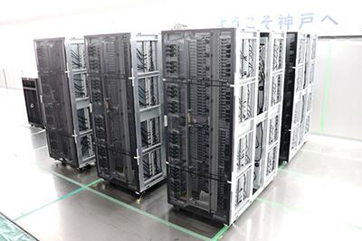 写真:計算機室内に運び入れられた6台の計算機ラック。後方の壁には「ようこそ神戸へ」の横断幕
